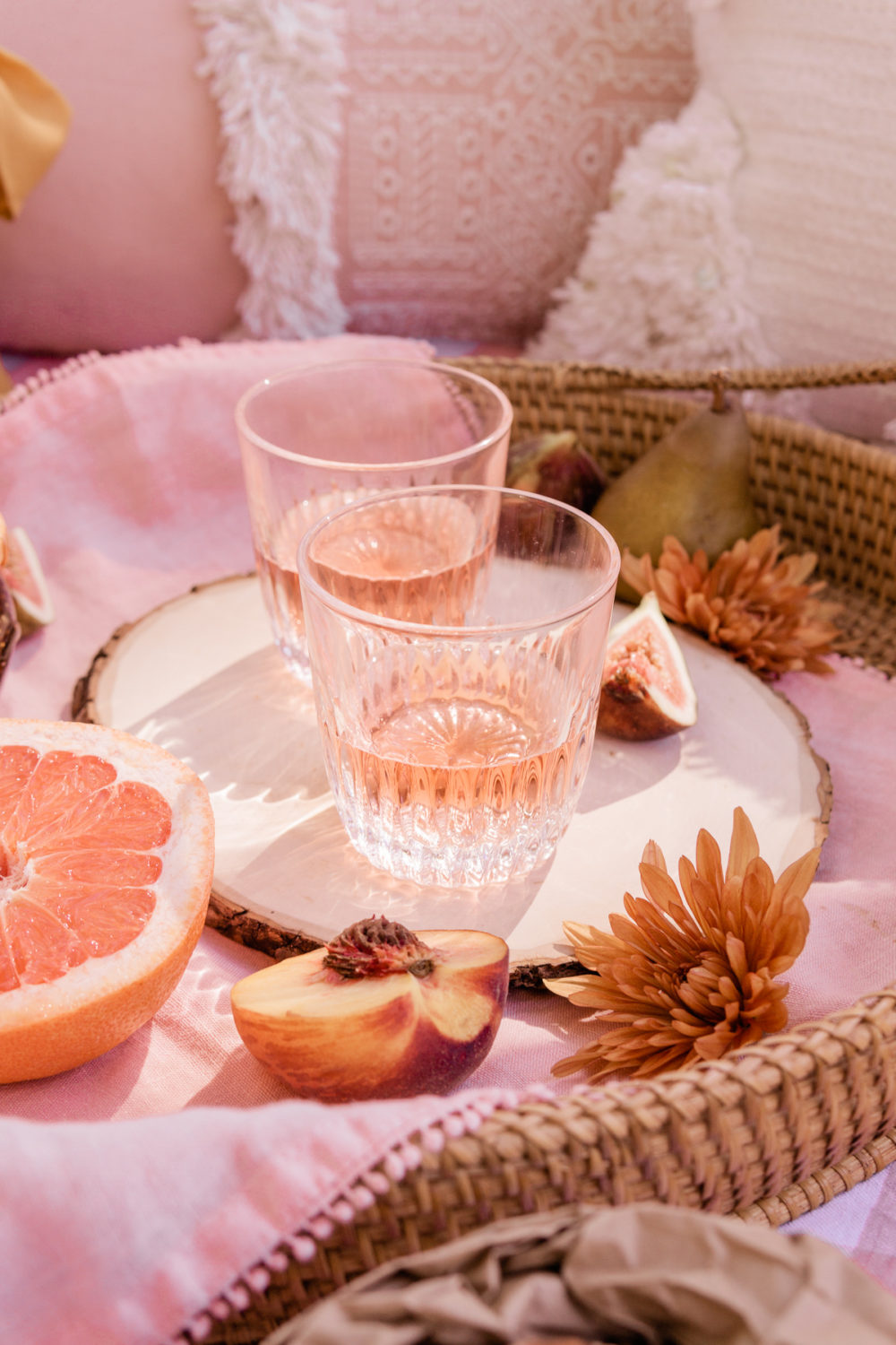 There are two glasses filled with rosé wine on top of a piece of wood onto of a pink napkin that is in a rattan tray. There are pink pillows in the background. There is also half a grapefruit, half a peach, and a sliced fig on the rattan tray